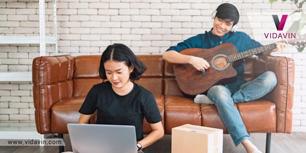 شوهری در حال نواختن گیتار برای همسر خود است