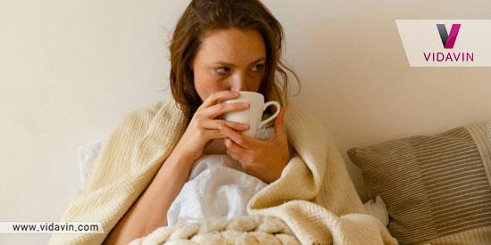 دختر بیمار در حال نوشیدن چای در بستر بیماری